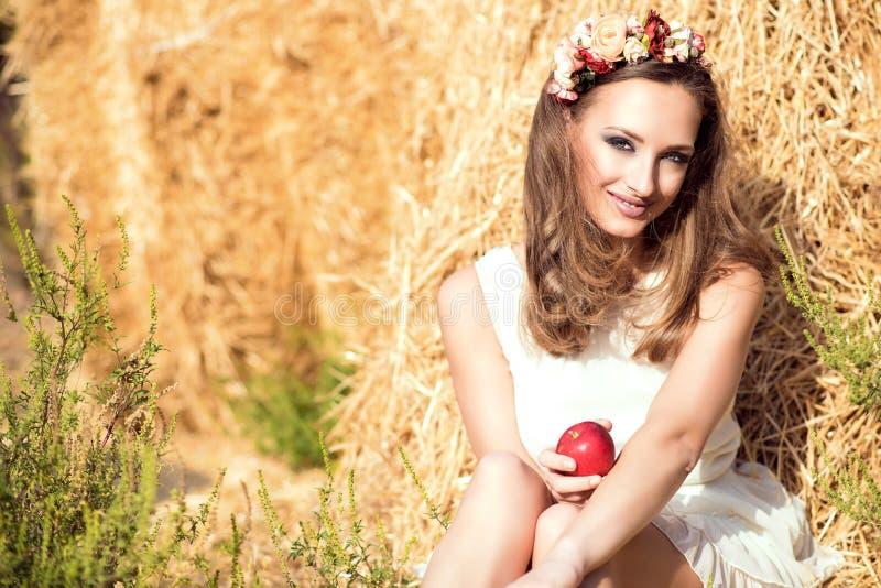 Schönes lächelndes tragendes weißes Sommerkleid des Mädchens und Blumenhauptkranz, die an den Heuschobern sitzt und einen roten A lizenzfreies stockfoto