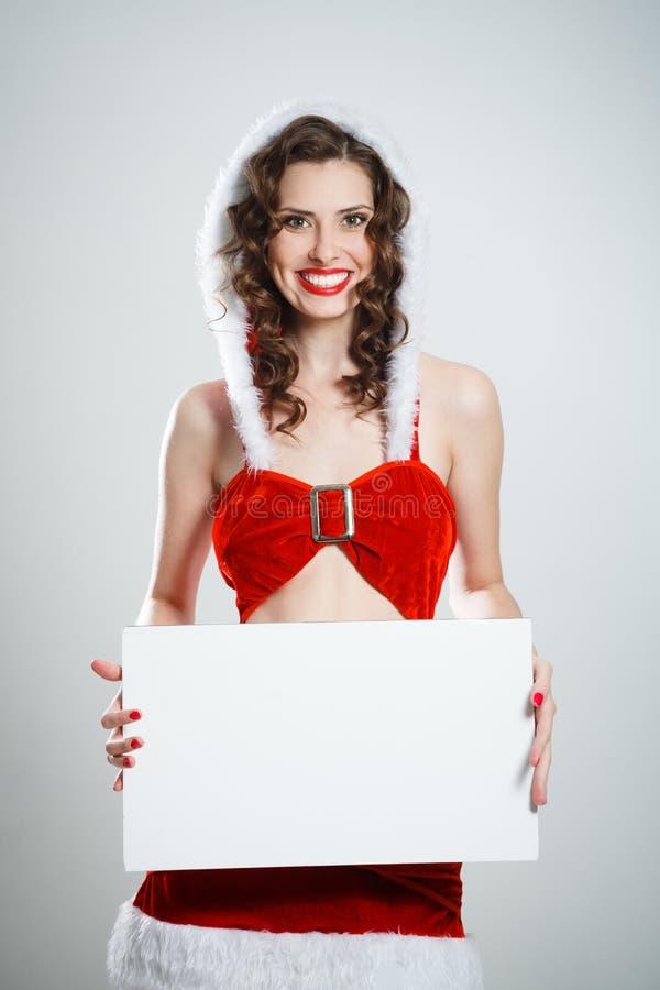 Schönes lächelndes Weihnachtsmädchen, das leeres Plakat hält lizenzfreie stockfotos