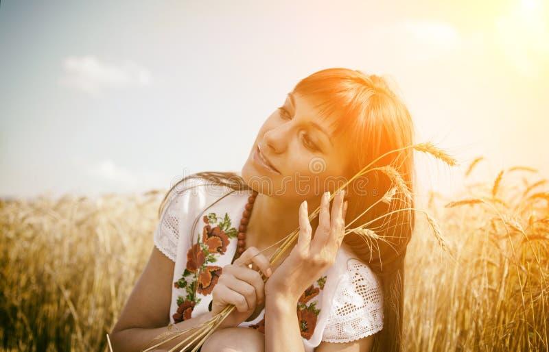 Schönes ländliches Mädchen auf dem Weizenfeld auf Sonnenuntergang lizenzfreie stockbilder