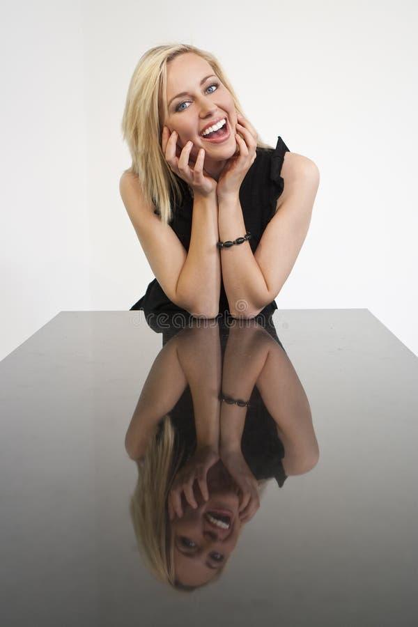 Schönes lachendes blondes Mädchen und ihre Reflexion stockbild