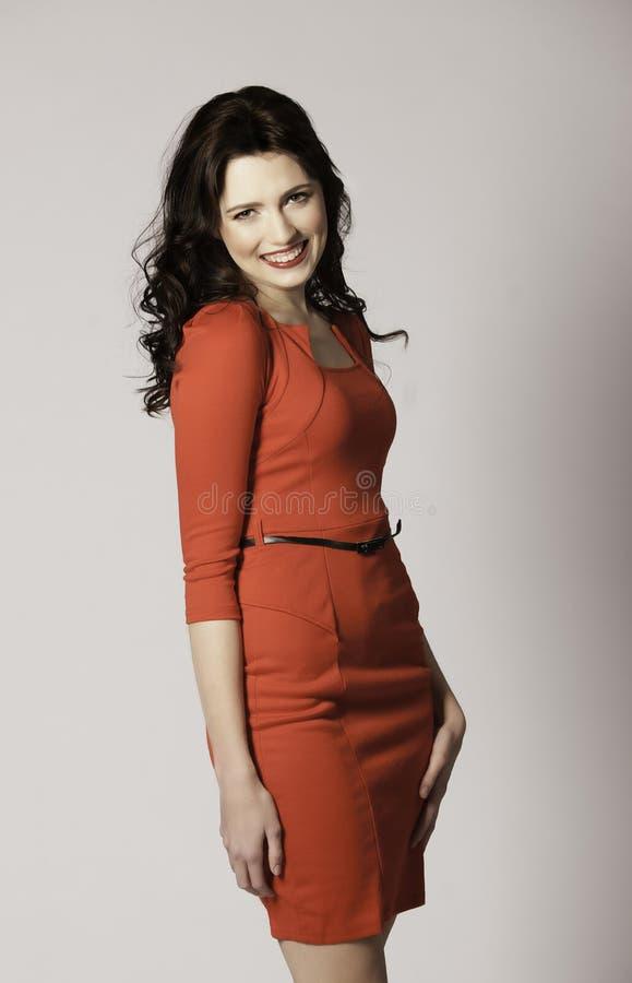Schönes lachendes Brunettemädchen im sexy roten Kleid stockfotos