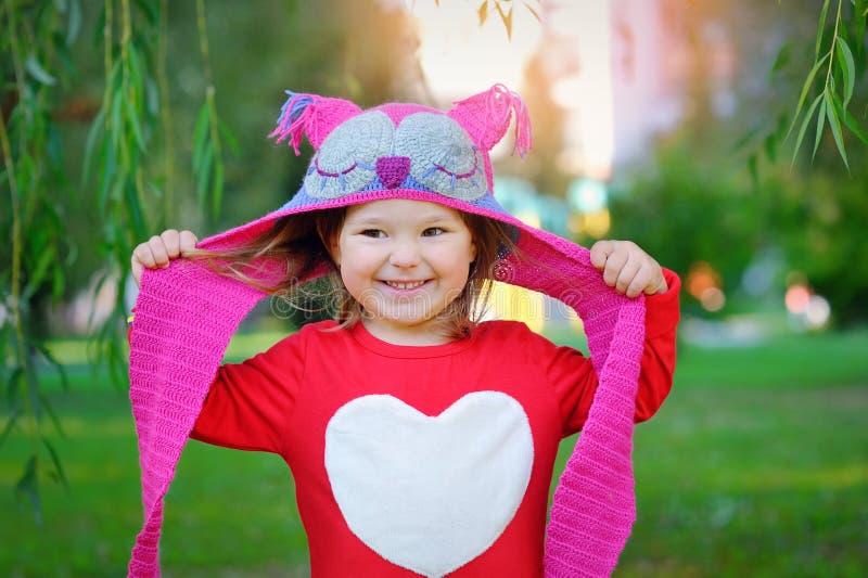 Schönes lachendes kleines Kleinkindmädchen in einem roten Mantel stockfoto