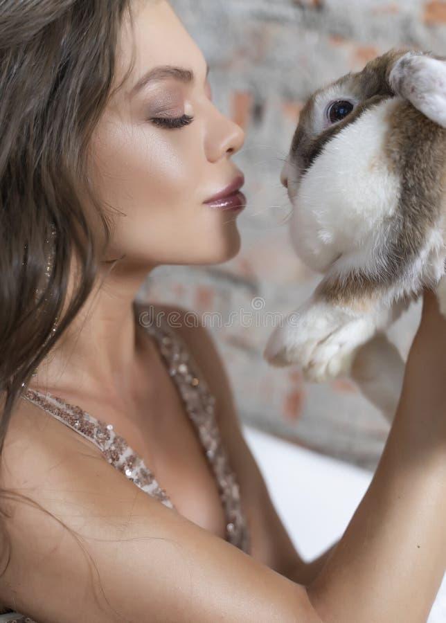 Schönes langbeiniges junges sexy elegantes Mädchen mit den großen Brüsten, ein glänzendes festes Kleid- und Ohrringe holda leicht stockbild