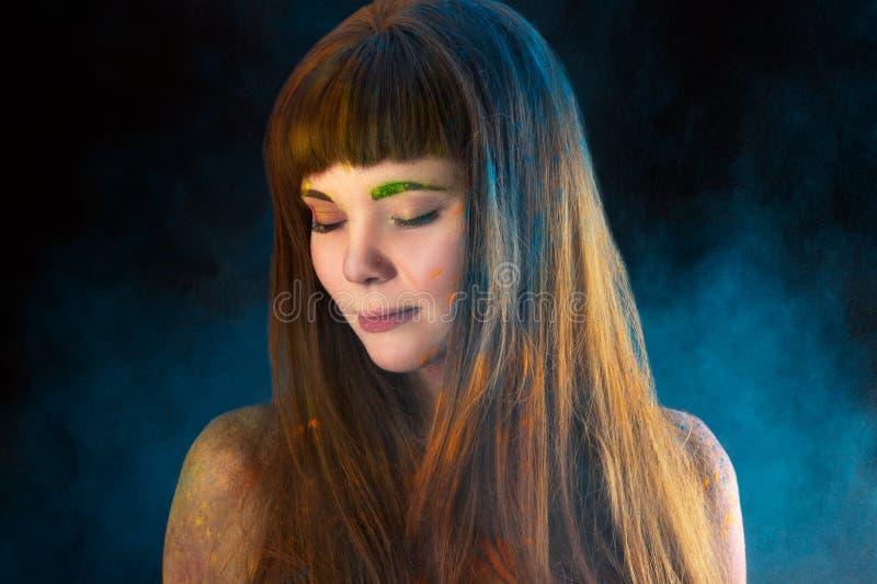 Schönes langhaariges Mädchen des Porträts in den Farben Holi lizenzfreie stockbilder