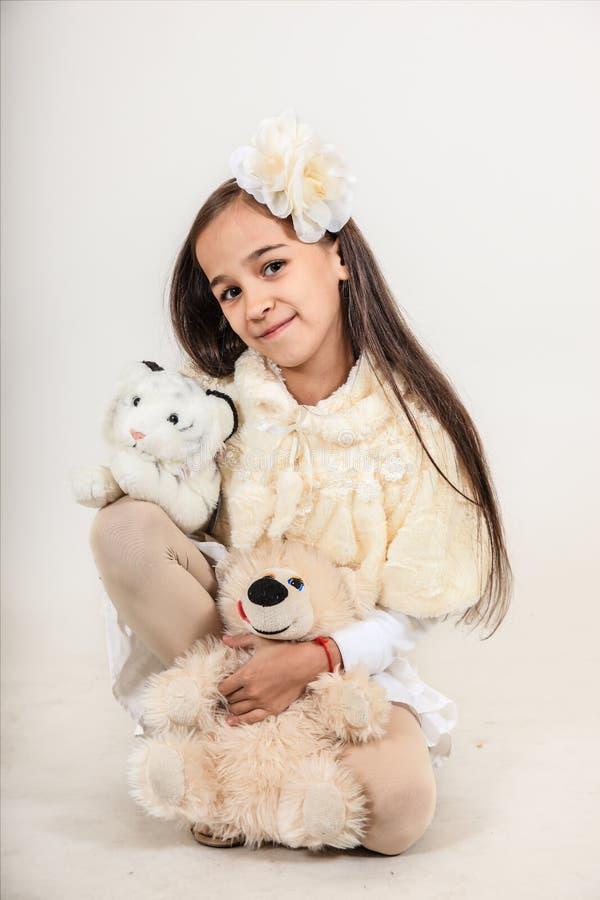 Schönes langhaariges Mädchen kleidete in einem weißen Mantel an Das Kind hält weiche Spielwaren auf lokalisiertem grauem Hintergr stockfotos
