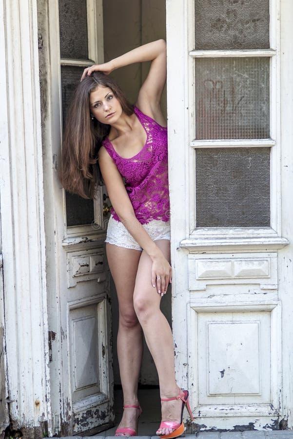 Schönes langhaariges Mädchen in transparentem Spitzen und wirft gegen eine Wand von Efeublättern auf stockfotografie