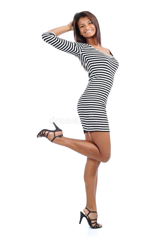 Schönes lateinamerikanisches Modell mit den langen Beinen, die eine Kleideraufstellung tragen stockbild