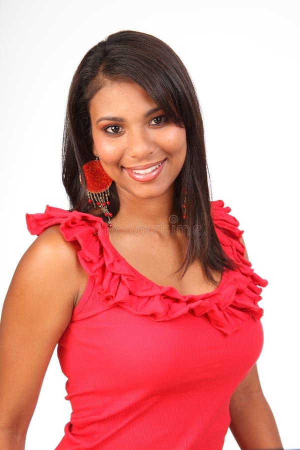 Schönes Latinomädchen in der roten Oberseite mit reizendem Lächeln lizenzfreies stockfoto
