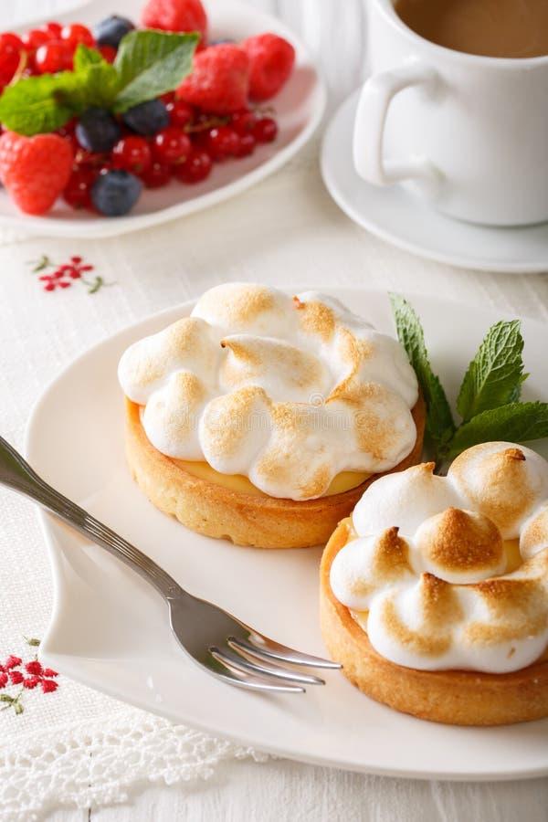 Schönes Lebensmittel: Zitronentörtchen mit Meringe und Kaffee, Beeren Clo lizenzfreie stockfotos