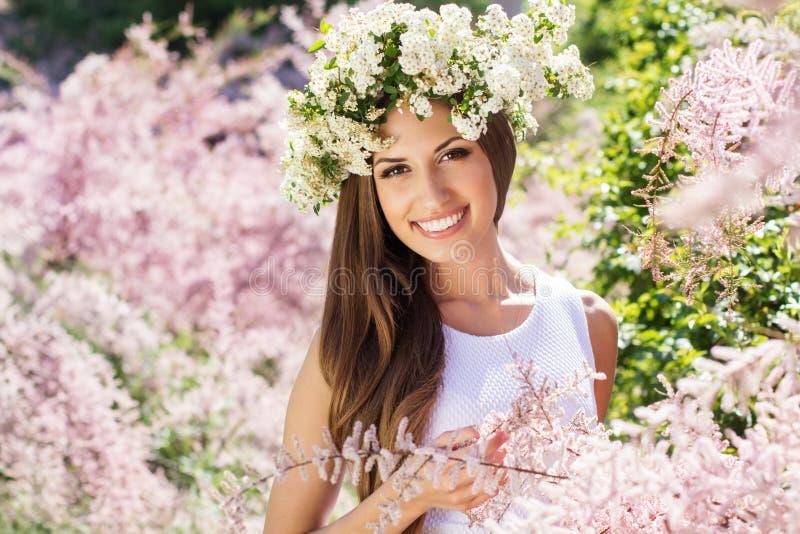 Schönes Mädchen auf der Natur im Kranz von Blumen lizenzfreie stockfotos