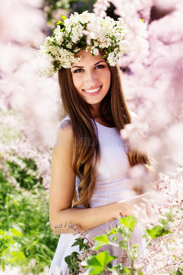 Schönes Mädchen auf der Natur im Kranz von Blumen stockfotografie