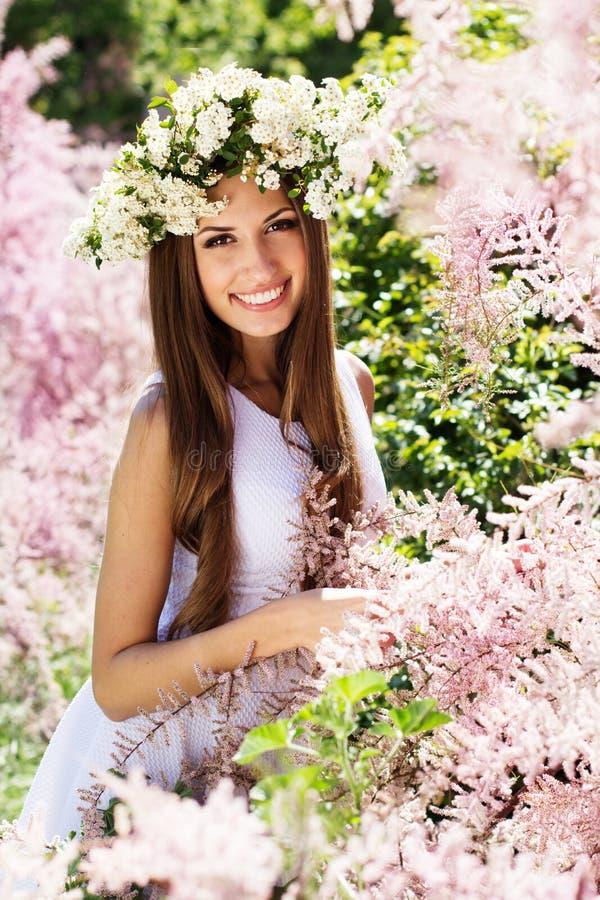 Schönes Mädchen auf der Natur im Kranz von Blumen lizenzfreie stockfotografie