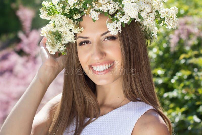 Schönes Mädchen auf der Natur im Kranz von Blumen stockfoto