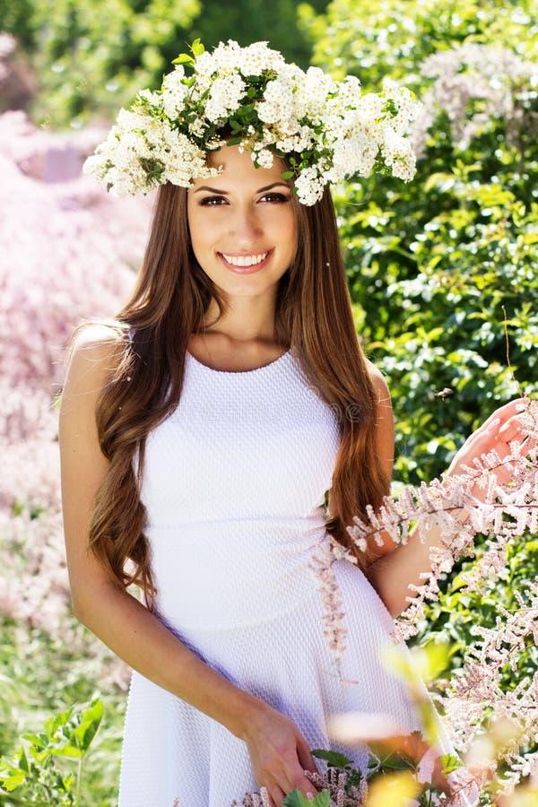 Schönes Mädchen auf der Natur im Kranz von Blumen stockbilder