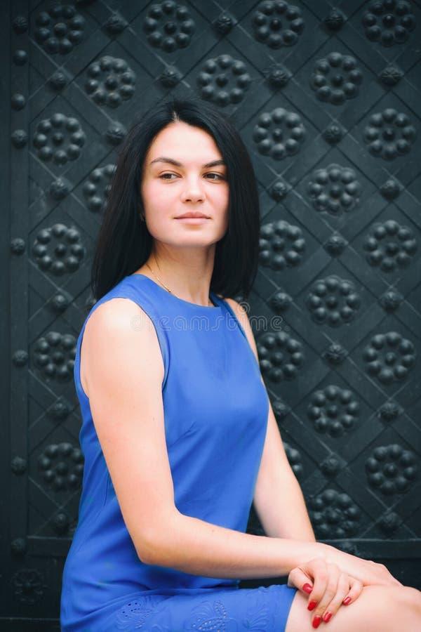 Schönes Mädchen auf schwarzes Metallaltem Türhintergrund lizenzfreie stockfotografie