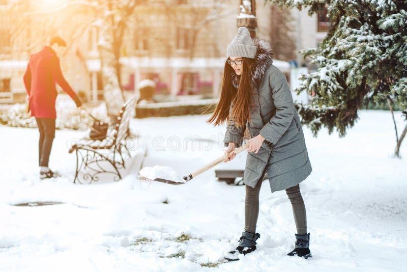 Schönes Mädchen auf Wintermode kleidet mit einer Schaufel stockbild