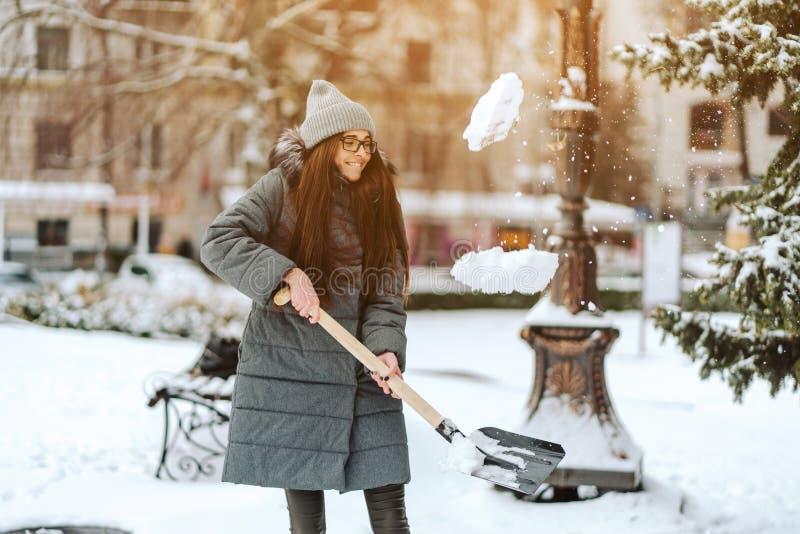 Schönes Mädchen auf Wintermode kleidet mit einer Schaufel stockfoto