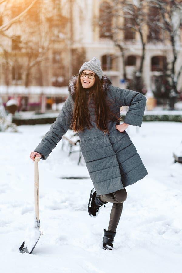 Schönes Mädchen auf Wintermode kleidet mit einer Schaufel lizenzfreies stockfoto