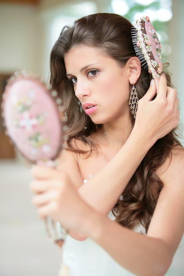 Schönes Mädchen behebt Frisur stockfotos