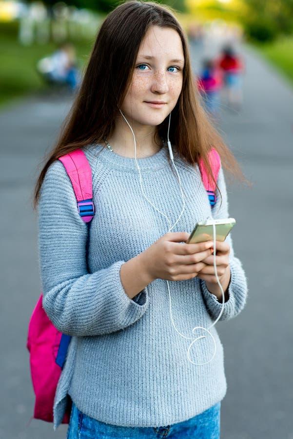 Schönes Mädchen Brunetteschulmädchen Sommer in der Natur Hinter Rückseite ist rosa Rucksack In den Händen des Telefons mit Kopfhö stockbilder