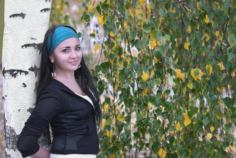 Schönes Mädchen, das allein nahe der Birke steht stockfotografie