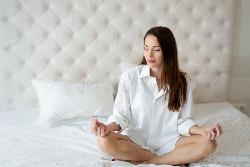 Schönes Mädchen, das auf übendem Yoga des Betts sitzt stockbilder