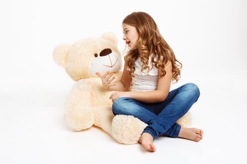 Schönes Mädchen, das auf Boden mit dem Spielzeugbären, Geschichte erzählend sitzt stockfotos