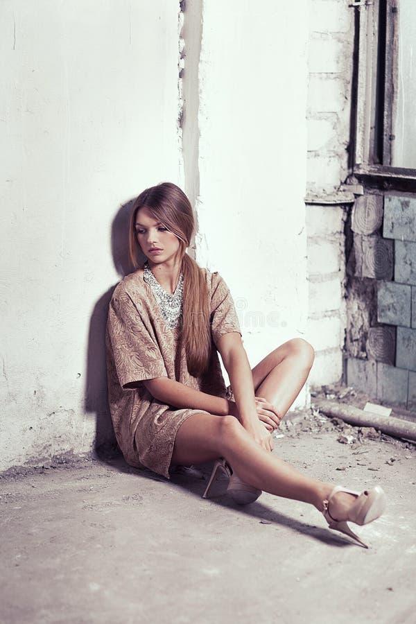 Schönes Mädchen, das auf dem Boden nahe dem Fenster sitzt lizenzfreie stockfotos