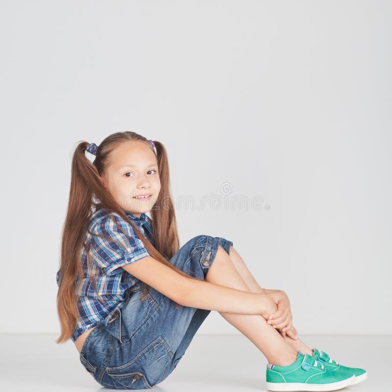 Schönes Mädchen, das auf dem Boden sitzt stockfotos