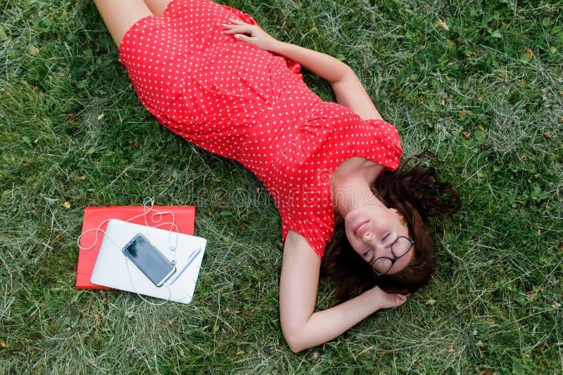 Schönes Mädchen, das auf dem Gras umgeben durch Geräte und Gerät liegt Beschneidungspfad eingeschlossen lizenzfreie stockbilder