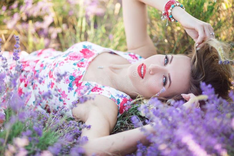 Schönes Mädchen, das auf dem Lavendelfeld liegt stockfotografie