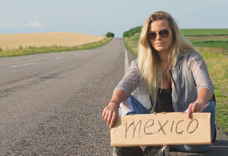Schönes Mädchen, das auf dem Straßenreisen per Anhalter fährt stockbilder