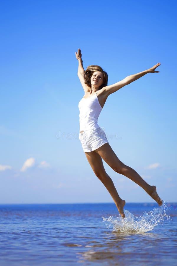 Schönes Mädchen, das auf den Strand springen stockbilder