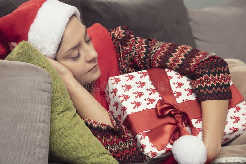 Schönes Mädchen, das auf der Couch, ein Geschenk in ihren Händen schläft lizenzfreie stockfotos