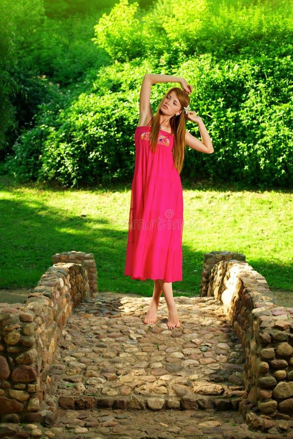 Schönes Mädchen, das auf der Felsenbrücke steht stockfotos