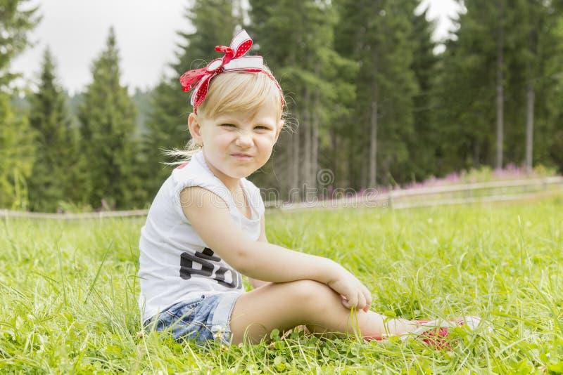 Schönes Mädchen, das auf der Wiese sitzt stockfoto
