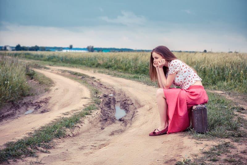 Schönes Mädchen, das auf eine Landstraße wartet stockfotografie