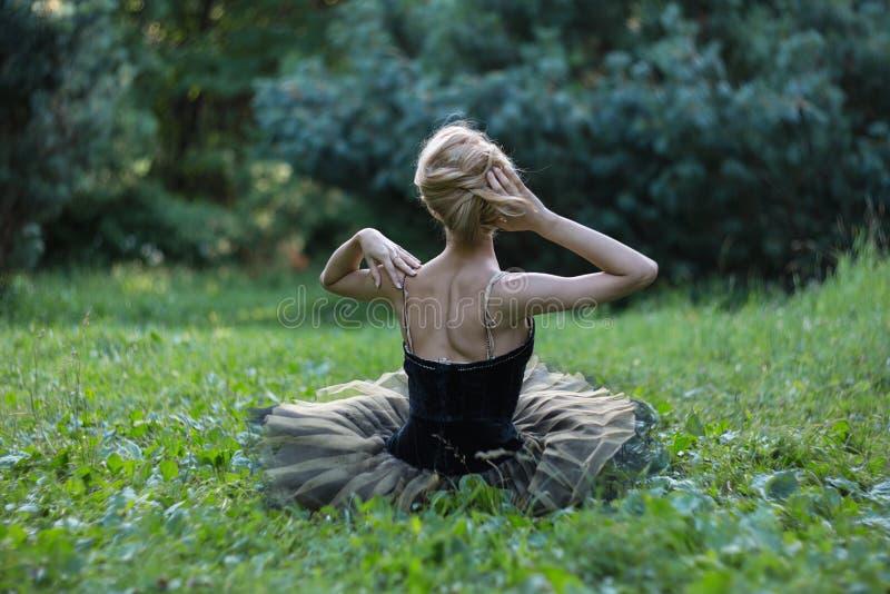 Schönes Mädchen, das auf einem Gras im Sommerpark liegt und stillsteht lizenzfreie stockfotografie