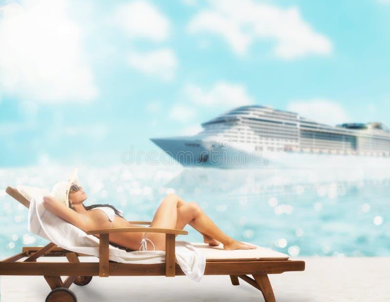 Schönes Mädchen, das auf einem Klappstuhl am Strand bei Sonnenuntergang mit cruiseship auf Hintergrund sitzt stockfotos