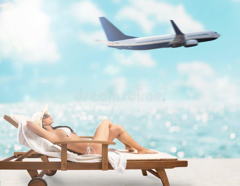 Schönes Mädchen, das auf einem Klappstuhl am Strand bei Sonnenuntergang mit Flugzeug auf Hintergrund sitzt lizenzfreie stockfotos