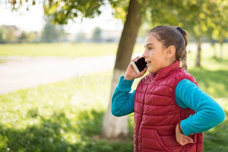 Schönes Mädchen, das auf einem Smartphone in der roten Weste spricht lizenzfreies stockbild