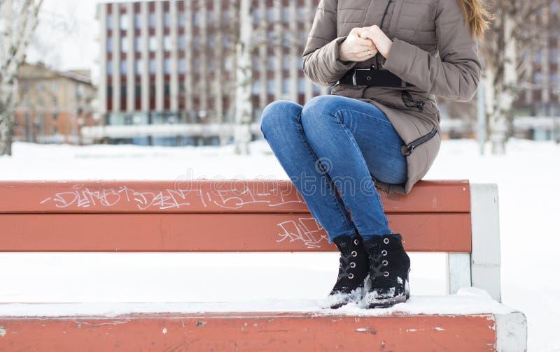 Schönes Mädchen, das auf einer Bank auf einem Stadthintergrund sitzt lizenzfreie stockfotografie