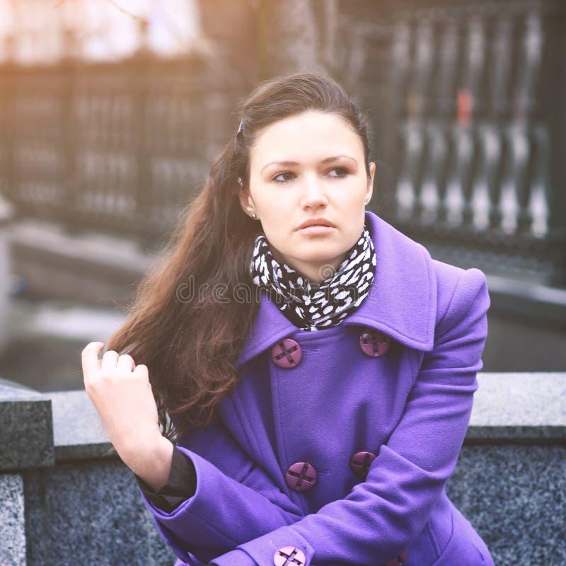 Schönes Mädchen, das auf einer Bank in fialetovom Mantel in der klaren Tageszeit sitzt lizenzfreies stockbild