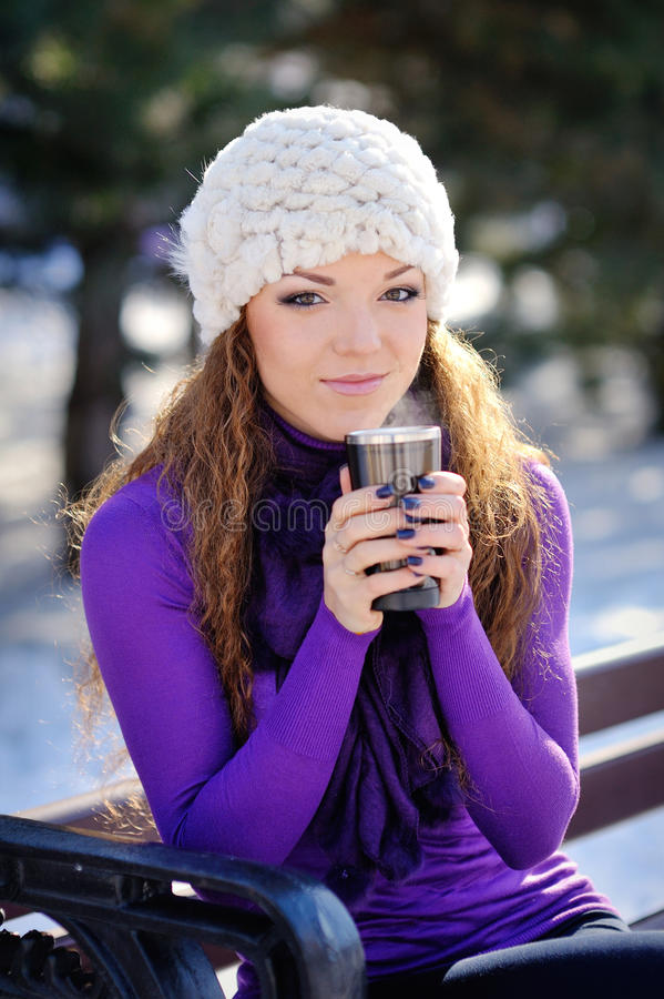 Schönes Mädchen, das auf einer Bank im Park mit einer Schale des Winters sitzt lizenzfreie stockfotos