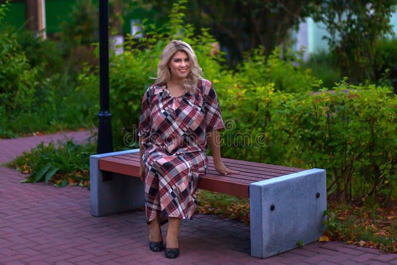 Schönes Mädchen, das auf einer Bank im Park sitzt lizenzfreie stockfotos