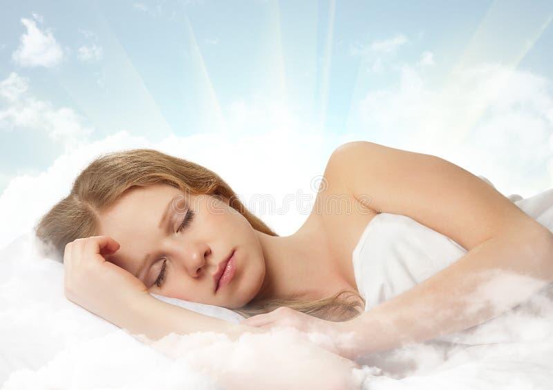 Schönes Mädchen, das auf einer Wolke im Himmel schläft lizenzfreie stockfotos