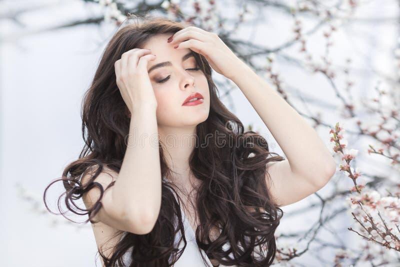 Schönes Mädchen, das an blühendem Baum im Garten über weißem Hintergrund sich entspannt und genießt stockfotos