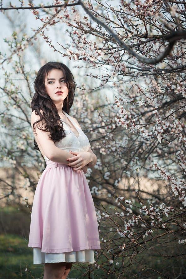 Schönes Mädchen, das an blühendem Baum im Garten steht lizenzfreies stockbild
