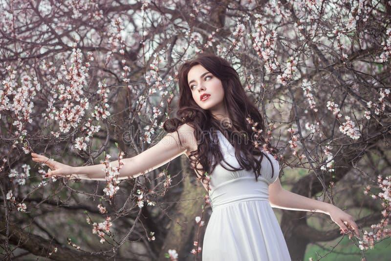 Schönes Mädchen, das an blühendem Baum im Garten steht stockfoto