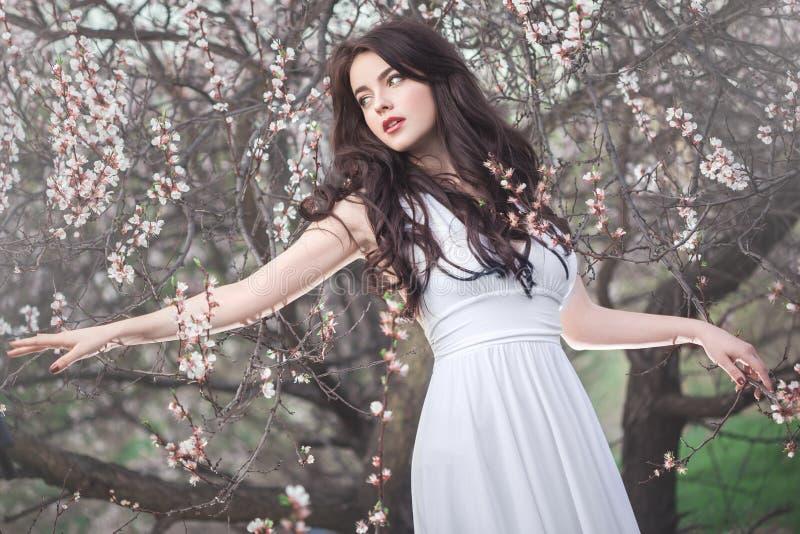 Schönes Mädchen, das an blühendem Baum im Garten steht lizenzfreie stockbilder
